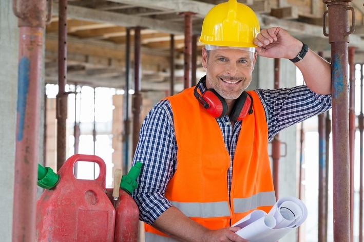 Happy Engineer With Blueprint On Site